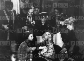 Origin Date: 1953-01-01 Annotation: Picture shows Marmeladoffs death scene from a 1953 BBC adaptatino fo Crime and Punishment by Dostoevsky. (Foreground): Frances Hyland as Sonia and Kenneth Hyde as Marmeladoff. (Background): Eugene Leachy as Coachman, Kenneth Griffin as Raskolnikoff, Ternece Greenidge, Dodd Mehan and Peter Augustine as the three men who brought Marmeladoff back and Sylvia Coleridge as an old woman. Personalities: Hyland, Frances; Hyde, Kenneth; Leahy, Eugene; Griffith, Kenneth; Greenidge, Terence; Mehan, Dodd; Augustine, Peter; Coleridge, Sylvia Location: GB Ref Number: 1438399